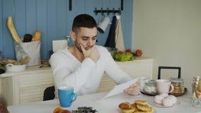 Uppriven läsningbokstav för ung man med den obetalda räkningen i köket hemma stock video