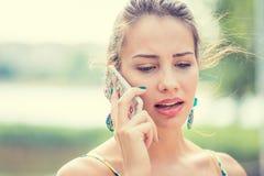 Uppriven ledsen skeptisk kvinna som talar på telefonen arkivbild