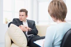Uppriven man som talar med psykologen Fotografering för Bildbyråer