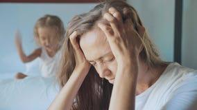 Uppriven moder med den ilskna skrikiga kudden för litet barn på bakgrunden stock video
