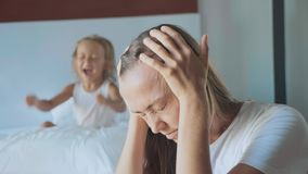 Uppriven moder med den ilskna skrikiga kudden för litet barn på bakgrunden lager videofilmer