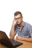 Uppriven och uttråkad pojke som framme sitter av hans bärbar dator Arkivfoto