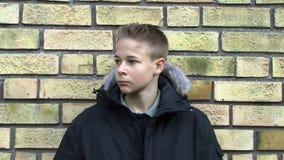 Uppriven pojke mot en vägg stock video