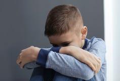 Uppriven preteen pojke som sitter på den gråa väggen royaltyfri foto