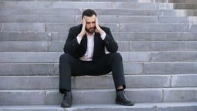 Uppriven ung affärsman som har spänning och sitter på trappa i gata Affärsman som har avtalsproblembegrepp royaltyfria bilder