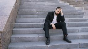 Uppriven ung affärsman som har spänning och sitter på trappa i gata Affärsman som har avtalsproblembegrepp royaltyfria foton
