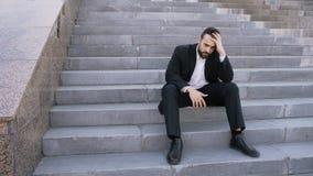 Uppriven ung affärsman som har spänning och sitter på trappa i gata Affärsman som har avtalsproblembegrepp royaltyfri fotografi