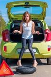 Uppriven ung flicka nära den brutna bilen Arkivbilder