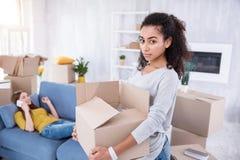 Uppriven ung flicka som packar upp medan hennes rumskamrat som talar på telefonen Fotografering för Bildbyråer