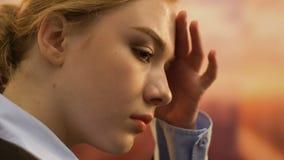 Uppriven ung kvinna med huvudvärk som tänker om arbetsproblem, fördjupning stock video