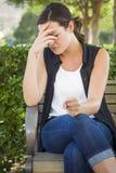 Uppriven ung kvinna som bara sitter på bänk arkivbild