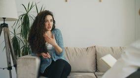 Uppriven ung kvinna som inomhus talar om hennes problem med den yrkesmässiga kvinnliga psykoanalytikern i psykoterapeutkontor