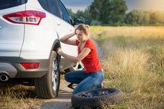 Uppriven ung kvinna som ser på det plana däcket av hennes bil på bygdvägen Arkivfoto