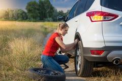 Uppriven ung kvinna som skruva av hjulmuttrar för att ändra det plana däcket på den öde bygdvägen Royaltyfri Fotografi