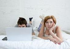 Uppriven unsatisfied för attraktiv kvinnakänsla och frustrerat i säng med hans make medan manarbetet på datorbärbara datorn som i royaltyfria foton