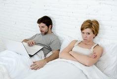 Uppriven unsatisfied för attraktiv kvinnakänsla och frustrerat i säng med hans make medan manarbetet på datorbärbara datorn som i royaltyfria bilder