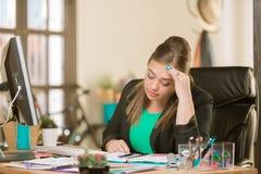 Uppriven yrkesm?ssig kvinna i ett id?rikt kontor royaltyfri foto