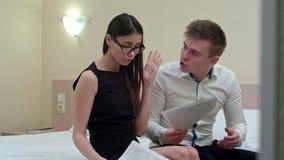 Upprivet kvinnaläsningdokument, medan mannen argumenterar med henne Arkivfoton