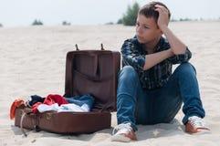 Upprivet sammanträde för tonårs- pojke på stranden nära resväskan arkivfoton