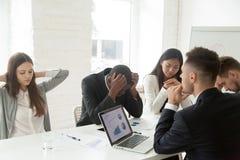 Upprivna kollegor som ner känner sig på grund av nyheterna för företagskonkurs arkivbild