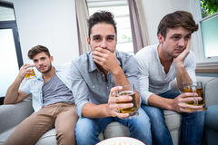 Upprivna manliga vänner som dricker alkohol, medan hålla ögonen på TV Royaltyfri Foto