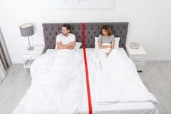 Upprivna par med förhållandeproblem som separat ligger i säng royaltyfri fotografi
