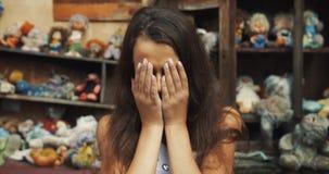 Upprivna små 10 år gammal flicka ser SAD kameran Henne isalmost gråt trädgård mycket av leksaker och gammalt möblemang stock video