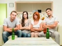 Upprivna vänner som håller ögonen på tv Royaltyfri Fotografi