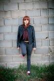 Upprorisk tonåringflicka med röd hårbenägenhet på en vägg Arkivbild
