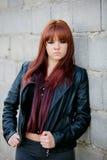 Upprorisk tonåringflicka med röd hårbenägenhet på en vägg Royaltyfri Bild