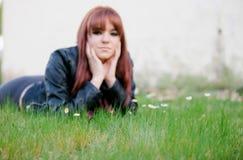 Upprorisk tonåringflicka med rött hår som ligger på gräset Royaltyfria Foton
