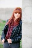 Upprorisk tonåringflicka med röd hårbenägenhet på en vägg Royaltyfri Fotografi