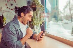 Upprymd man som pumpar näven, medan se den mobila smartphonen arkivbild