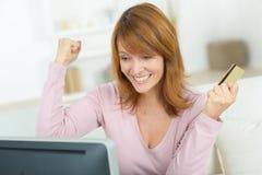Upprymd vinnare som segrar hållande ögonen på den direktanslutet bärbara datorn hemma royaltyfri fotografi