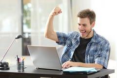 Upprymd vinnareman som hemma använder en bärbar dator fotografering för bildbyråer