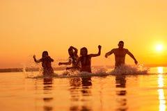 Upprymda vänner som simmar i afton royaltyfri foto