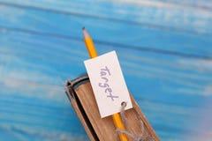 Uppsätta som mål tecknet på pancil och den gamla boken - tappningstil Fotografering för Bildbyråer
