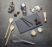 Uppsättning av aromatiska kryddor, sesamfrö, salt, socker och kitchenware, på grå färger Arkivfoton