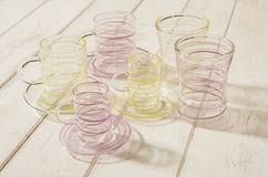 Uppsättning av att dricka exponeringsglas med guling- och lilastrimmadesigner Arkivbild