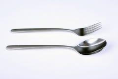 Uppsättning av bestick Belägga med metall gaffeln och skeda med det matte handtaget på vit bakgrund Arkivfoto
