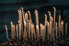 Uppsättning av bränningstearinljus i kyrkan, Italien Arkivfoto