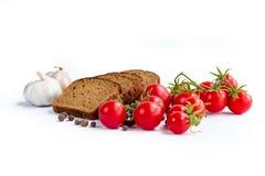 Uppsättning av brödskivor, körsbärsröda tomater och vitlök Royaltyfri Fotografi