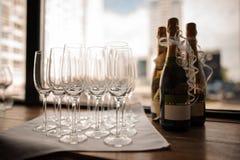 Uppsättning av champagneflaskor och tomma vinexponeringsglas på servetten Arkivbilder