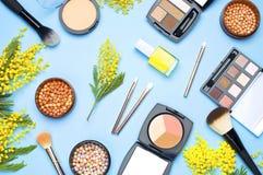 Uppsättning av dekorativa skönhetsmedel för korrigeringsen Brushes för ögonskugga för sminkpulverrouge och blommor av mimosan på  Arkivfoto