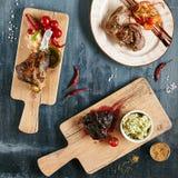 Uppsättning av den huvudsakliga kursen för restaurang med grillade nötköttkinder, lammben royaltyfria foton