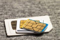 Uppsättning av den kortkort-, mikro och nano simcarden Isolerat på grå torkduketext arkivbilder