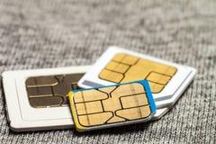 Uppsättning av den kortkort-, mikro och nano simcarden på grå torkduketext royaltyfri bild