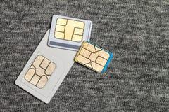 Uppsättning av den kortkort-, mikro och nano simcarden på grå torkduketext royaltyfri foto