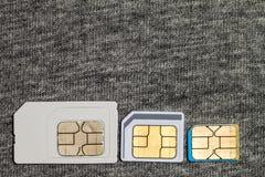Uppsättning av den kortkort-, mikro och nano simcarden på grå torkduketext royaltyfria bilder