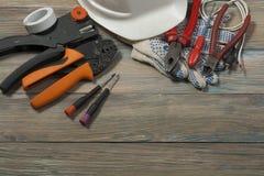 Uppsättning av det elektriska hjälpmedlet på träbakgrund Tillbehör för teknikarbete, energibegrepp royaltyfri fotografi